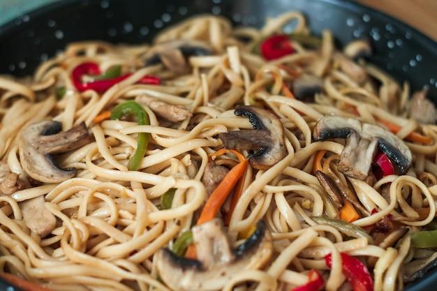 Cucina cinese tradizionale. mescolare le tagliatelle fritte con le verdure. avvicinamento.
