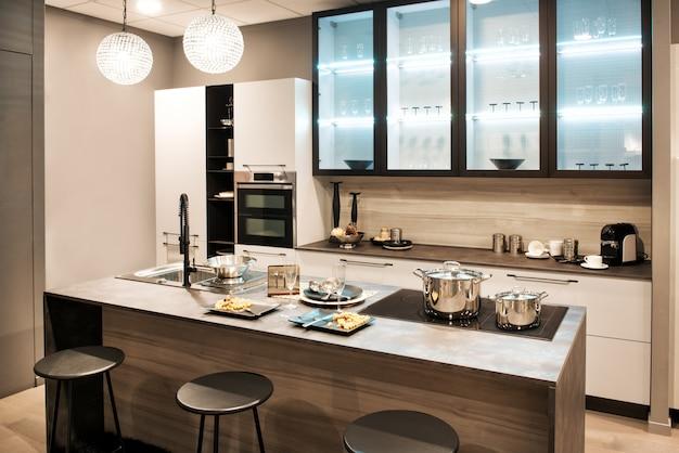 Cucina componibile neutra con isola e sgabelli da bar