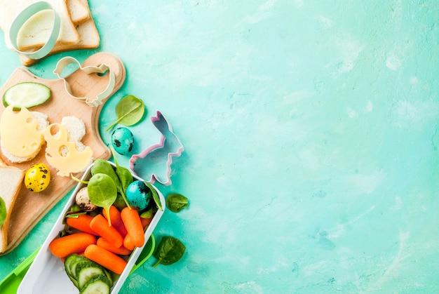Cucina creativa per bambini colazione box pranzo per pasqua, panini con formaggio, verdure fresche - cetrioli, carote, spinaci, uova di quaglia colorate. tavolo azzurro, copia spazio vista dall'alto
