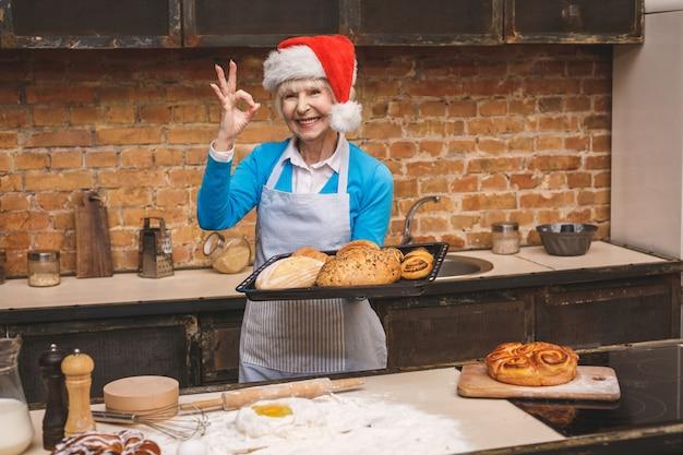 Cucina di capodanno. il ritratto della donna invecchiata senior attraente sta cucinando sulla cucina. nonna che produce cottura saporita di natale.