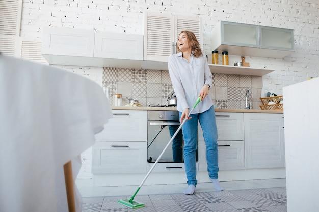 Cucina di pulizia della giovane donna