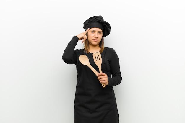 Cucina la donna con uno sguardo serio e concentrato, confrontando le idee e pensando a un problema stimolante contro il muro bianco