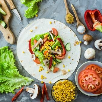 Cucina messicana di burrito vegano - verdure e funghi su tortillas