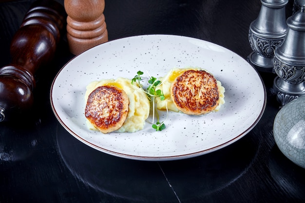 Cucina moderna. chiuda sulla vista sulla cotoletta del servizio del ristorante dal tacchino sulla purè di patate con micro verde sul piatto bianco. concetto di cibo sano. carne grigliata. burger. disteso