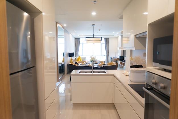 Cucina moderna con elettrodomestici in monolocale con zona pranzo e soggiorno combinati