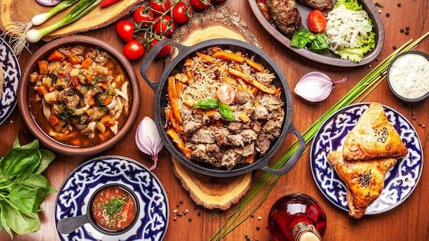Cucina orientale tradizionale uzbeka. tavolo della famiglia uzbeka di diversi piatti per le vacanze di capodanno.