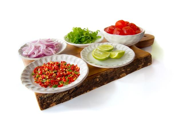 Cucina tailandese ingrediente di insalata salata piccanti piccanti scalogni di insalata, salari, limone, peperoncino rosso, uovo salato su tagliere di legno