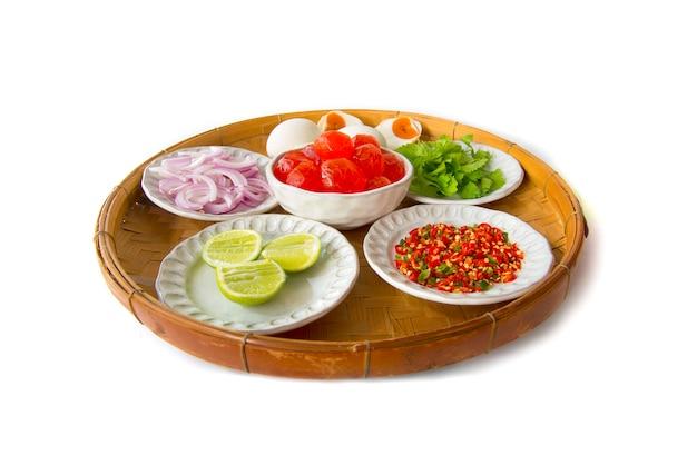 Cucina tailandese ingrediente di scalogno piccante salato tuorlo d'uovo insalata, salari, limone, peperoncino rosso, uovo salato sul cestello di bambù trebbiatura
