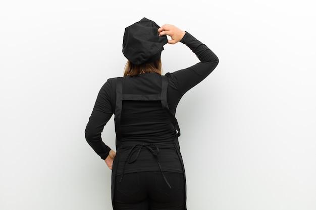 Cucina una donna che si sente incapace e confusa, pensando a una soluzione, con la mano sull'anca e l'altra sulla testa, vista posteriore
