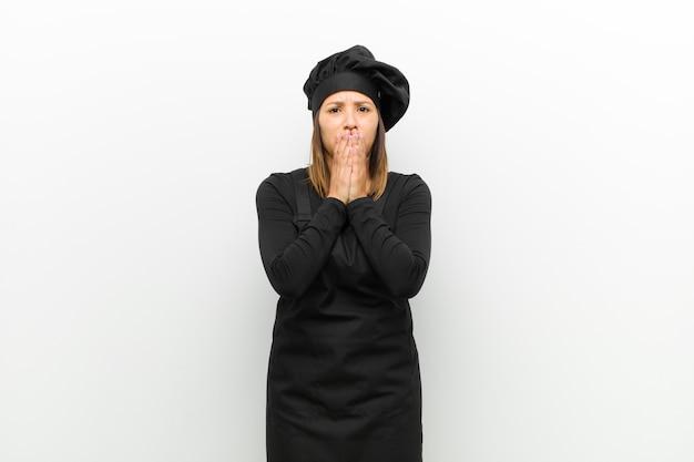 Cucina una donna che si sente preoccupata, turbata e impaurita, coprendosi la bocca con le mani, guardando ansiosa e incasinata