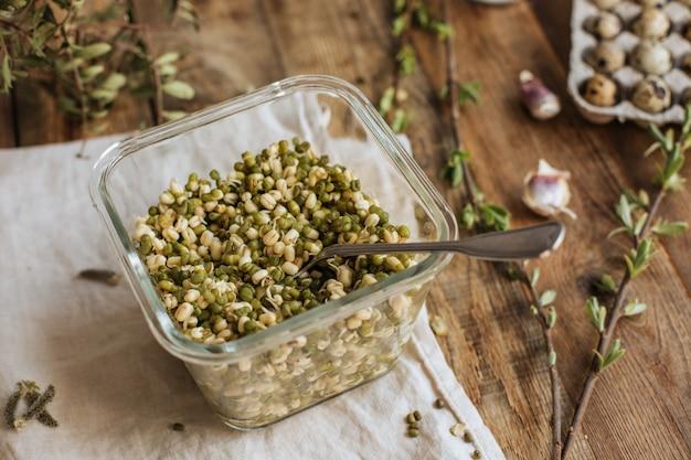 Cucina vegana. fagioli asiatici germogliati in un barattolo di vetro su una tavola di legno.