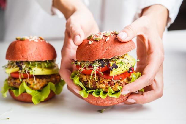 Cucinando gli hamburger rosa del vegano con la cotoletta, l'avocado ed i germogli dei fagioli su bianco