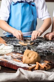 Cucinando i biscotti del pan di zenzero di natale su un'oscurità.
