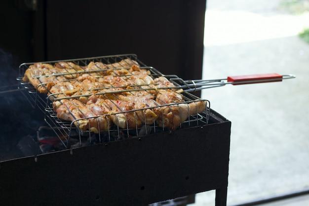 Cucinando le coscie di pollo nell'alimento all'aperto della vacanza estiva della griglia