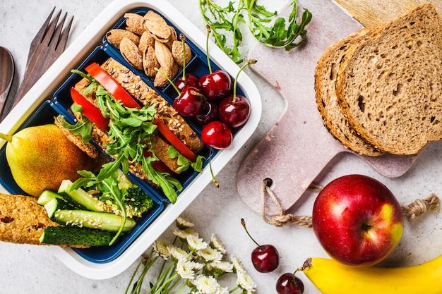 Cucinare cibi sani nella scatola del pranzo. panino, frutta, snack in grigio