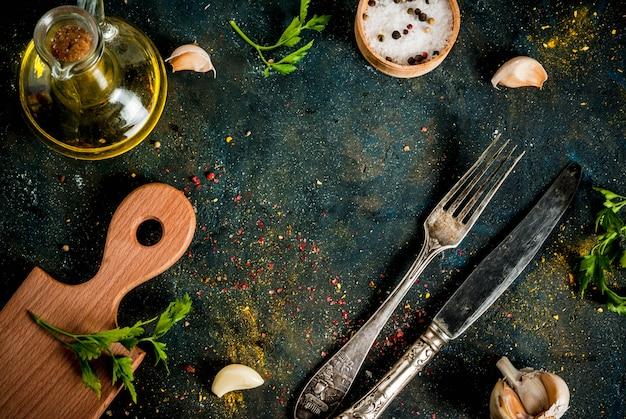 Cucinare concetto di cibo, spezie, erbe e olio per preparare la cena, con tagliere