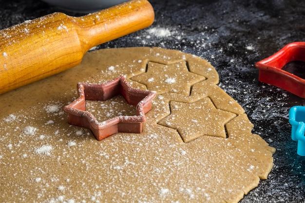 Cucinare i biscotti di panpepato di natale con il mattarello su una superficie scura
