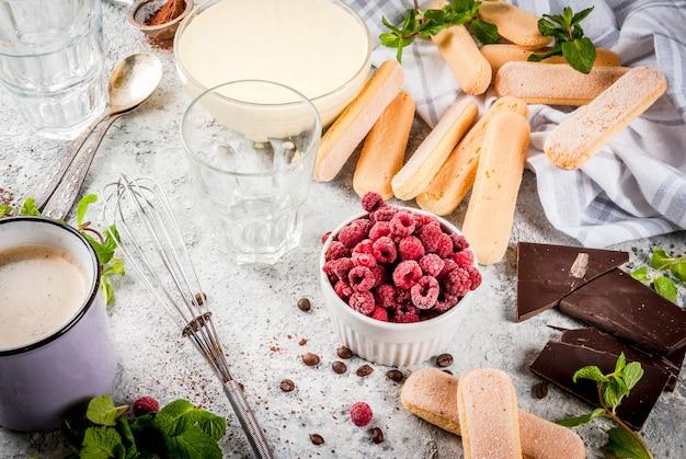 Cucinare il dessert italiano tiramisu con tutti gli ingredienti necessari caffè al cacao mascarpone con menta e lamponi