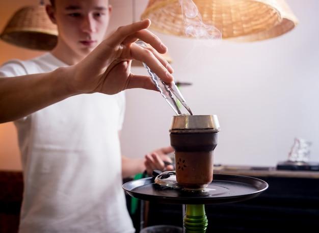Cucinare il narghilè nel bar. giovane con narghilè in ristorante, bar narghilè, caffè fumatori.