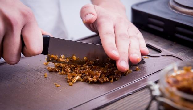 Cucinare il narghilè nel bar. tagliare il tabacco in una ciotola. ristorante, bar con narghilè, bar per fumatori.