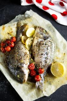 Cucinare il pesce in forno. dorado di cottura con pomodorini ed erbe su pergamena nel forno.