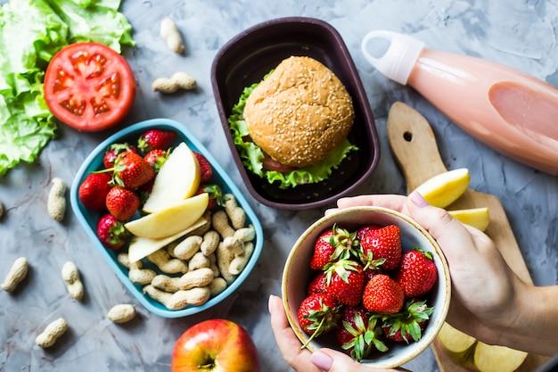 Cucinare il pranzo per il bambino a scuola. sul tavolo della cucina grigia