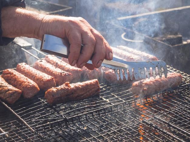 Cucinare la carne barbecue. mititei rumeno e cotto alla griglia nel fumo.