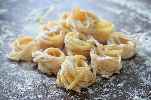 Cucinare la pasta fatta in casa italiana su sfondo scuro