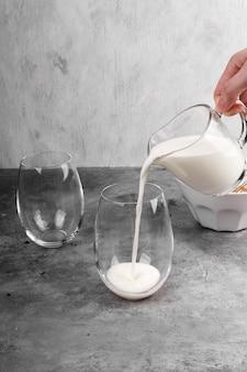 Cucinare passo dopo passo un famoso caffè coreano dalgon. versare il latte nel bicchiere di caffè su uno spazio grigio
