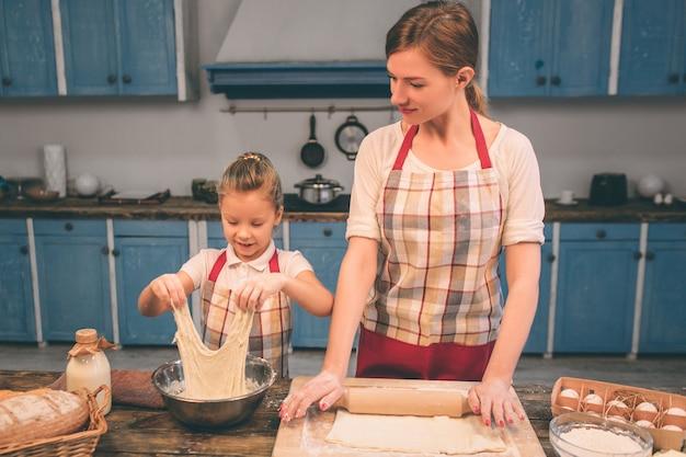 Cucinare torte fatte in casa. la famiglia amorosa felice sta preparando insieme il forno. la ragazza della figlia del bambino e della madre sta cucinando i biscotti e si sta divertendo nella cucina. arrotolare l'impasto.