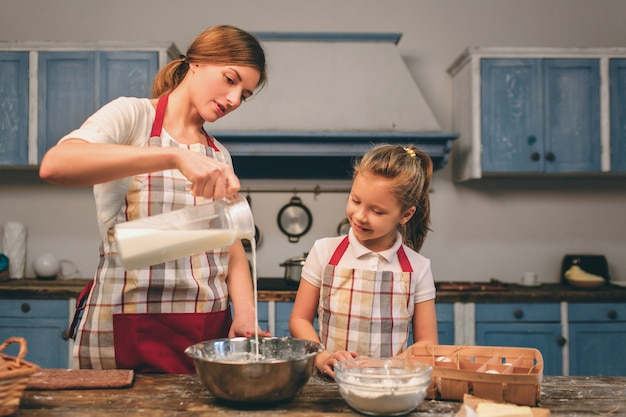 Cucinare torte fatte in casa. la famiglia amorosa felice sta preparando insieme il forno. la ragazza della figlia del bambino e della madre sta cucinando i biscotti e si sta divertendo nella cucina. latte per pasta, ingredienti in una ciotola