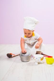 Cucini il bambino che si siede con gli utensili della cucina sul pavimento