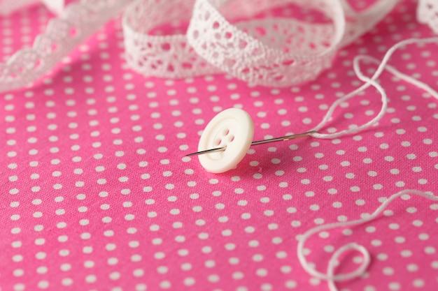 Cucire il bottone sul panno a pois