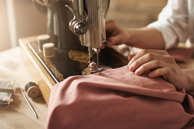 Cucire mi rilassa la mente. colpo potato del sarto femminile che lavora al nuovo progetto, facendo i vestiti con la macchina per cucire in officina, essendo occupato. giovane designer che realizza le sue idee