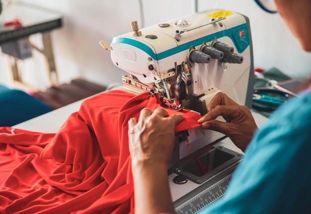 Cucitrice asiatica al lavoro su una macchina da cucire