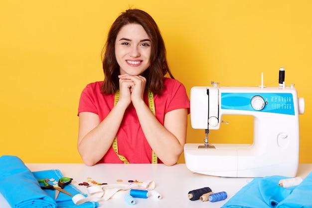 Cucitrice attraente felice della giovane donna che si siede al tavolo di lavoro