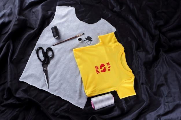 Cucitura di magliette per bambini con disegno fatto a mano. tessuto grigio e giallo su un buio