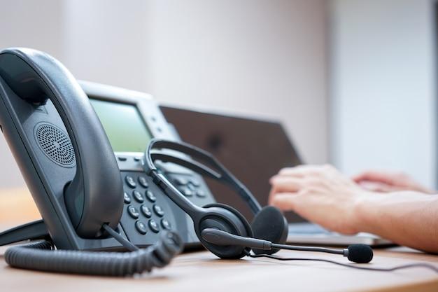 Cuffia avricolare con sfocato della mano degli impiegati del call center che lavora nella stanza in funzione
