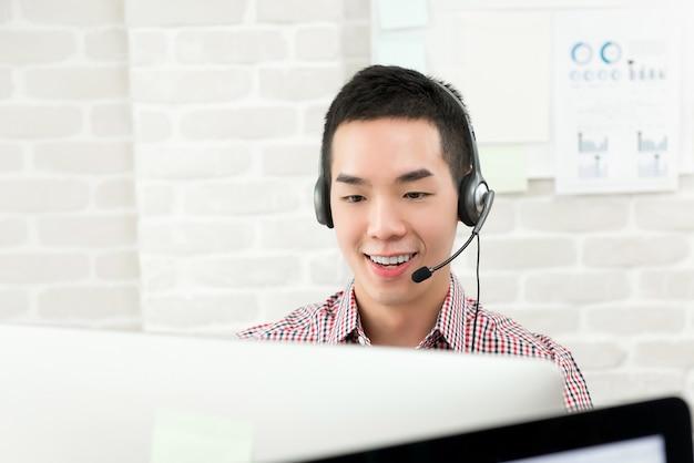 Cuffia avricolare d'uso del microfono dell'uomo d'affari asiatico che funziona come agente di servizio di assistenza al cliente di vendita per televisione, concetto di lavoro della call center