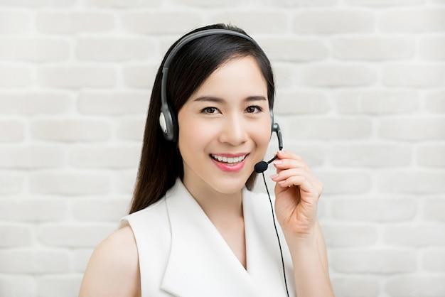 Cuffia avricolare d'uso del microfono della donna di affari asiatica casuale come agente di servizio di assistenza al cliente di vendita per televisione