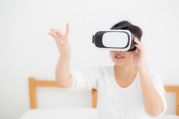 Cuffia avricolare d'uso di realtà virtuale della bella giovane donna asiatica allegra e divertente