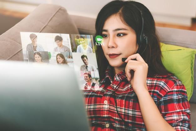 Cuffia avricolare d'uso e conferenza d'uso della donna asiatica di affari con la gente di affari nel lavoro dal concetto di distanziamento sociale domestico