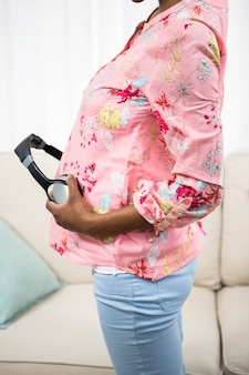 Cuffia della tenuta della donna incinta sulla pancia sullo strato