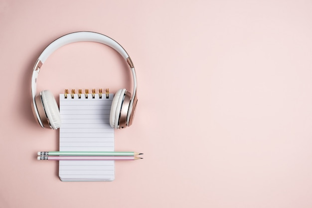 Cuffia rosa, blocco note in bianco e matite su fondo rosa, vista superiore