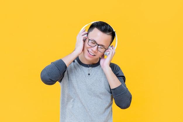 Cuffie d'uso dell'uomo asiatico felice che ascoltano la musica di rilassamento con gli occhi chiusi isolato sulla parete gialla