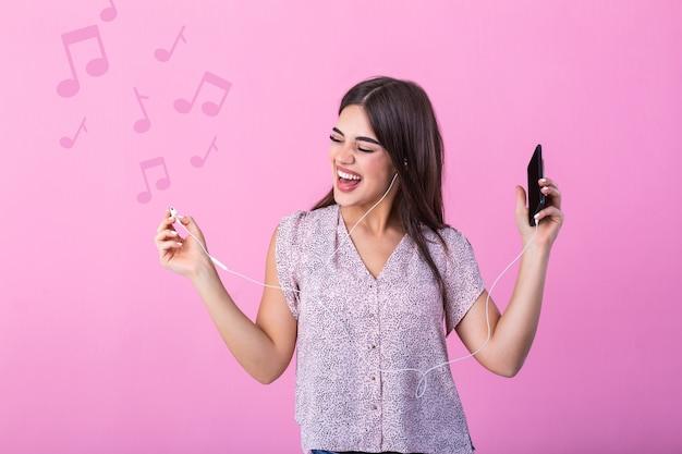 Cuffie d'uso della giovane donna felice che ascoltano la musica dallo smartphone