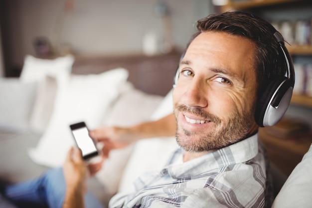 Cuffie da portare sorridenti dell'uomo mentre sedendosi sul sofà