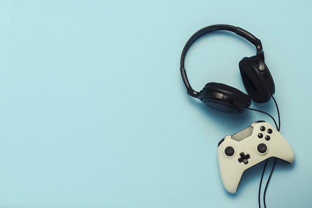 Cuffie e gamepad su uno sfondo blu. . concetto di giochi per computer, intrattenimento, giochi, tempo libero. vista piana, vista dall'alto