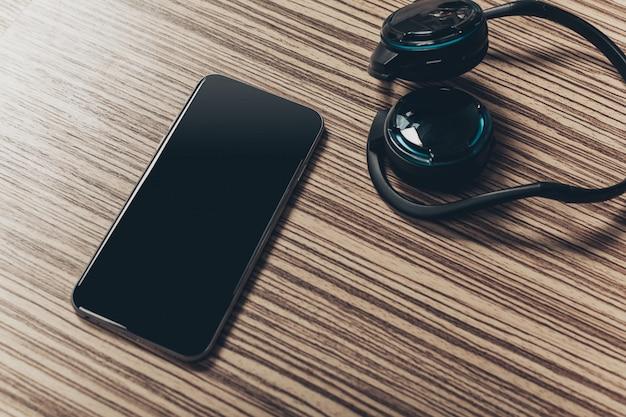 Cuffie e smart phone su legno