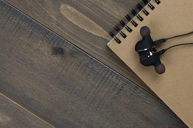 Cuffie e taccuino sullo scrittorio di legno con lo spazio della copia.